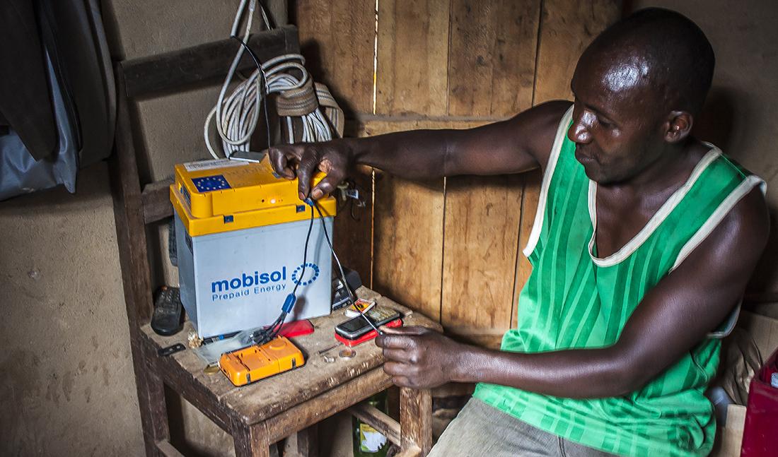 Bonde med Mobisolbatteri på den rwandiska landsbygden.